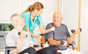 nurse helping two senior men exercise